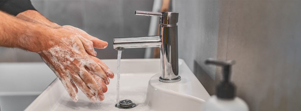 Man washing hands to prevent spreading COVID-19.