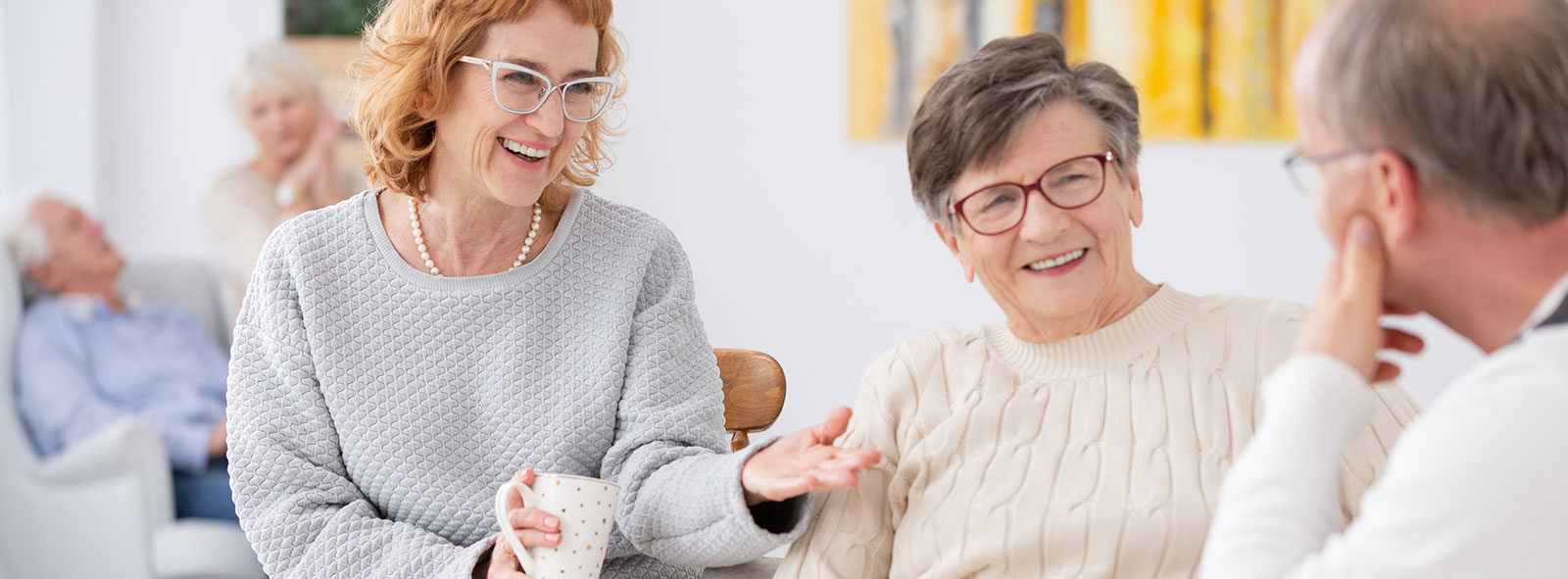 elderly people at assisted living facility talking and enjoying each other's company