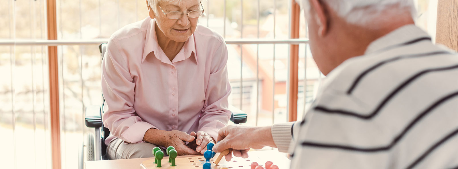 Elderly white couple at memory care facility playing chess